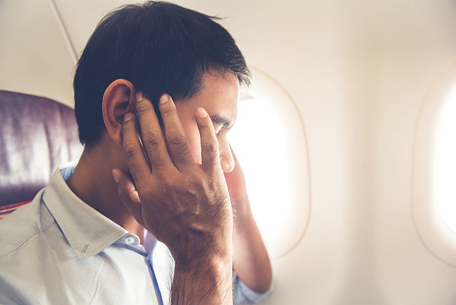 You can ease ear pain while flying by chewing gum or using pressure-relieving earplugs.